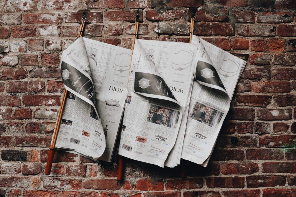 Image d'illustration montrant trois journaux accrochés sur un mur de brique.